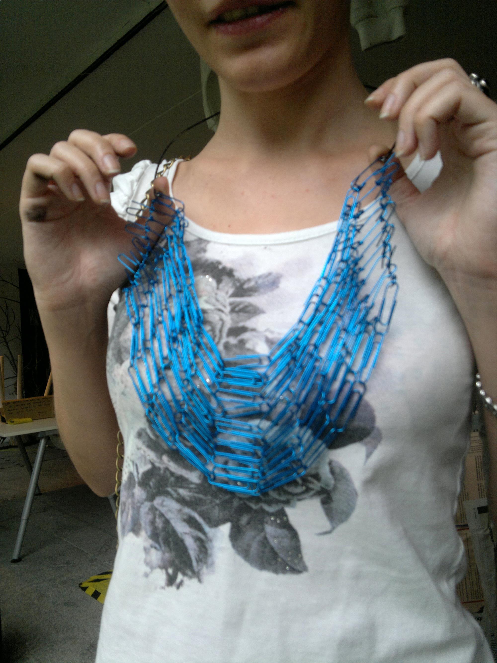 Procrastinar creando un collar de clips azules de oficina.